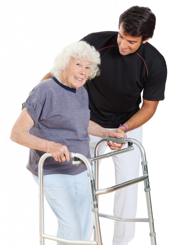 Portrait of a happy senior woman holding walker while trainer assisting her over white background